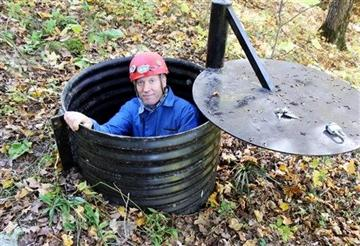 (AP Photo/Jeff Baenen). In this  Oct. 10, 2013, photo, John Ackerman poses in a shaft entrance to his Temple of Doom, one of the 37 caves on his property near Spring Valley, Minn.