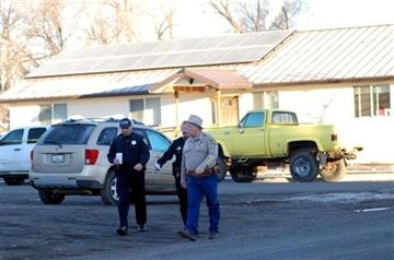 (AP Photo/Jeff Barnard). Modoc County Sheriff and Coroner Mike Poindexter, right, walks away from the Cedarville Rancheria tribal headquarters building in Alturas, Calif., on Friday, Feb. 21, 2014.