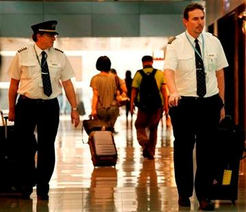 (AP Photo/Vincent Yu, File). In this  Nov. 30, 2011 photo, two pilots from Cathay Pacific walk in the Hong Kong International Airport in Hong Kong.