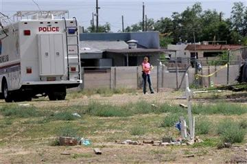 (AP Photo/Albuquerque Journal, Jim Thompson). In a Saturday, July 19, 2014 photo, Albuquerque police work at the scene where two men were found dead in a open area just north of Central Avenue at 60th Street.