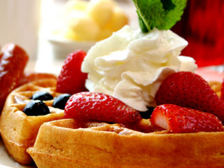 Top waffles with strawberries and whipped cream for a colorful presentation.  &amp;copy; istockphoto.com