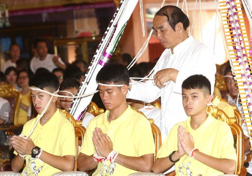 (AP Photo/Sakchai Lalit). Soccer coach Ekkapol Janthawong, center, and members of the rescued soccer team attend a Buddhist ceremony that is believed to extend the lives of its attendees as well as ridding them of dangers and misfortunes in Mae Sai dis...