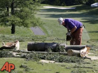 A worker chainsaws a tree that fell onto a tee box on the 12th hole at Congressional Country Club in Bethesda, MD, Saturday after a strong storm blew through overnight. (AP Photo/Patrick Semansky)
