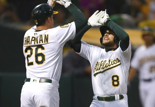 (AP Photo/Ben Margot). Oakland Athletics' Jed Lowrie, right, celebrates with Matt Chapman (26) after hitting a two-run home run off Seattle Mariners' Felix Hernandez in the third inning of a baseball game Tuesday, Aug. 14, 2018, in Oakland, Calif.
