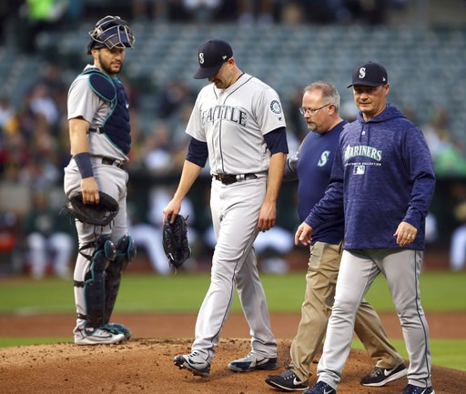 (AP Photo/Ben Margot). Seattle Mariners pitcher James Paxton, second from left, is escorted off the field after being hit by a ball in the first inning of a baseball game against the Oakland Athletics Tuesday, Aug. 14, 2018, in Oakland, Calif.