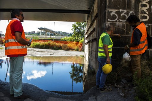 (AP Photo/Nicola Marfisi). Workers inspect the the area around the collapsed Morandi highway bridge, in Genoa, northern Italy, Wednesday, Aug. 15, 2018. A bridge on a main highway linking Italy with France collapsed in the Italian port city of Genoa du...