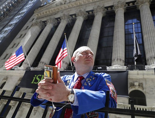 (AP Photo/Kathy Willens, File). FILE- In this April 26, 2018, file photo, Vincent Pepe enjoys some fresh air outside the New York Stock Exchange where he works trading cotton shares for VLM Commodities in the Financial District in New York. The U.S. st...