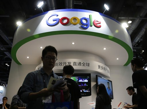 (AP Photo/Andy Wong, File). FILE - In this April 28, 2016, file photo, visitors gather at a display booth for Google at the 2016 Global Mobile Internet Conference (GMIC) in Beijing. Google employees are upset with the company's secretive plan to build ...
