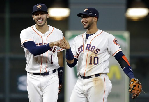 (AP Photo/David J. Phillip). Houston Astros shortstop Carlos Correa (1) reacts with second baseman Yuli Gurriel (10) after fielding a ground ball by Colorado Rockies' Tony Wolters and throwing to first for the out during the ninth inning of a baseball ...