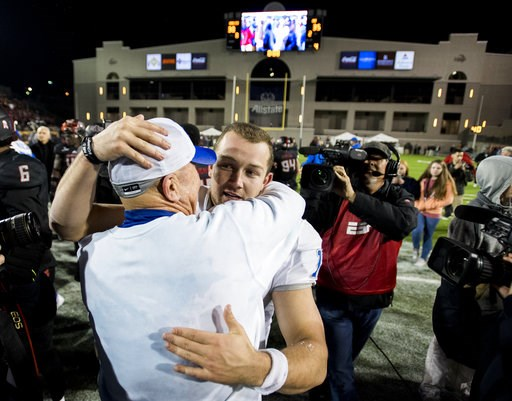 (Mickey Welsh/The Montgomery Advertiser via AP, File). FILE - In this Dec. 16, 2017, file photo, Middle Tennessee head coach Rick Stockstill hugs his son, quarterback Brent Stockstill (12), after beating Arkansas State in the Camellia Bowl NCAA college...