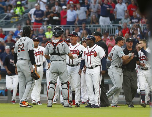 (AP Photo/John Bazemore). Miami Marlins catcher J.T. Realmuto (11) stands between pitcher Jose Urena (62) and Atlanta Braves manager Brian Snitker (43) as the dugouts empty after Urena hit Braves' Ronald Acuna Jr. with a pitch during the first inning o...