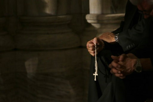 (AP Photo/Mary Altaffer, File). FILE- In this Sept. 24, 2015, file photo a member of the clergy prays the rosary as he waits for Pope Francis to arrive at St. Patrick's Cathedral for evening prayer service in New York. Across the U.S., Catholics once f...
