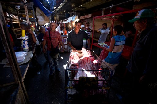 (AP Photo/Fernando Llano). A butcher pushes beef ribs to sell at Las Pulgas market in Maracaibo, Venezuela, Sunday, Aug. 19, 2018. Venezuelans are bracing for a 3,000 percent hike in the minimum wage on Monday, leaving one butcher contemplating firing ...