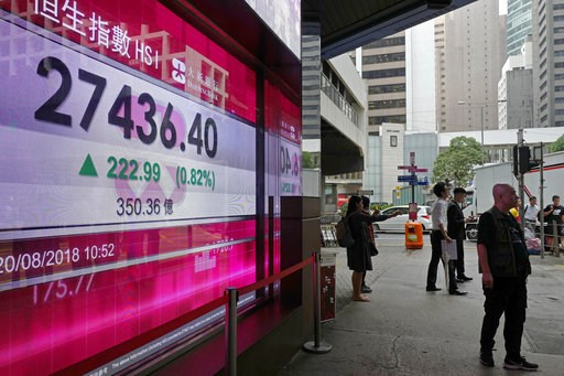 (AP Photo/Vincent Yu). People walk past an electronic board showing Hong Kong share index outside a local bank in Hong Kong, Monday, Aug. 20, 2018. Asian stocks are mostly higher Monday as investors welcomed signs of progress in resolving the trade dis...