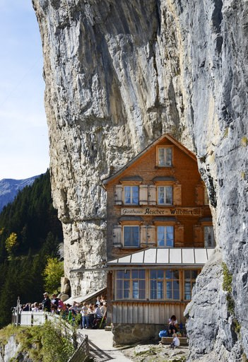 (Steffen Schmidt/Keystone via AP). FILE - In this Oct. 14, 2014 file photo people take a break outside the Gasthaus Aescher near Ebenalp, Switzerland. The Gasthaus Aescher, built into a cliff above a valley in northeastern Switzerland, has been run by ...