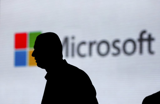 (AP Photo/Altaf Qadri, File). FILE - In this Nov. 7, 2017, file photo, a man is silhouetted as he walks in front of Microsoft logo at an event in New Delhi, India. Microsoft says it's uncovered new Russian hacking attempts targeting U.S. political grou...
