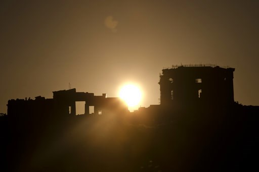 (AP Photo/Petros Giannakouris). The sun rises behind Propylaea, the monumental gate of the ancient Acropolis hill, left, and the 2500 BC Parhenon temple in Athens, on Tuesday, Aug. 21, 2018.