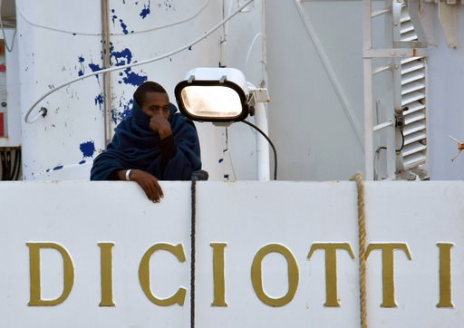 """(Orietta Scardino/ANSA via AP). A man stands on the deck of the Italian Coast Guard ship """"Diciotti"""" moored at the Catania harbor Tuesday, Aug. 21, 2018. The European Union is trying to find countries willing to take 177 people rescued at sea after Ital..."""