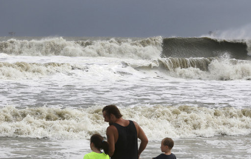 (AP Photo/Dan Anderson). Laura Cunningham, 10,left, Hunter Shows, center, and Brandon Perry, 10, right, watch the waves crash from Tropical Storm Gordon on Tuesday, Sept. 4, 2018 in Dauphin Island, Ala.