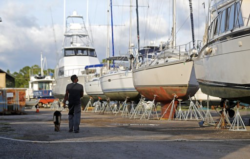 (AP Photo/Gerald Herbert). Manuel Arias walks with a guard dog, Toto, past boats that were dry-docked inland in preparation for Tropical Storm Gordon, expected to make landfall as a hurricane later in the evening, in Pass Christian, Miss., Tuesday, Sep...
