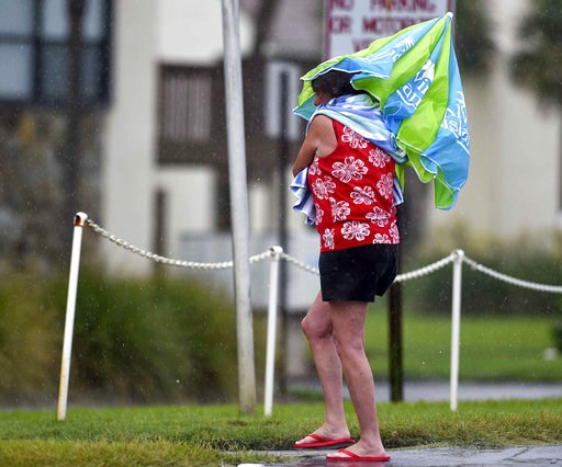 (Devon Ravine/Northwest Florida Daily News via AP). A woman uses a beach umbrella to stay dry as she crosses Scenic Highway 98 in Miramar Beach, Fla., Tuesday Sept. 4, 2018, as Tropical Storm Gordon makes its way past the Florida Panhandle.