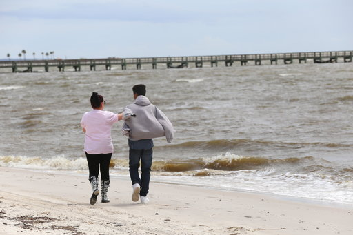 (John Fitzhugh/The Sun Herald via AP). Krystal Flanagan, left, of Biloxi, Miss., and her son, Desmond Dentley, walk on the beach in Biloxi on Tuesday, Sept. 4, 2018, as Tropical Storm Gordon heads toward the Mississippi coast. The storm could strengthe...