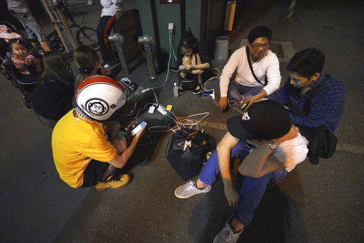 (AP Photo/Eugene Hoshiko, File). FILE - In this Thursday, Sept. 6, 2018, file photo, people gather to charge their mobile phones in the blackout on the center of Sapporo, Hokkaido, northern Japan, after a powerful earthquake. The blackouts that paralyz...