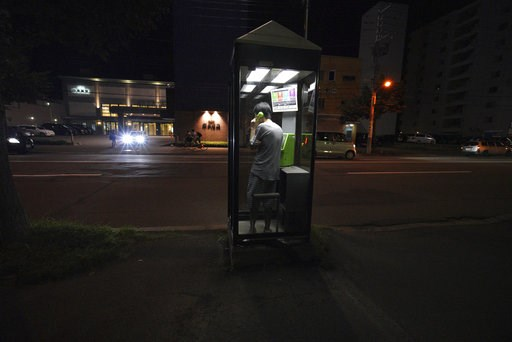 (AP Photo/Eugene Hoshiko, File). FILE - In this Thursday, Sept. 6, 2018, file photo, a man calls with a public phone in the blackout on the center of Sapporo city, Hokkaido, northern Japan, after a powerful earthquake. The blackouts that paralyzed the ...