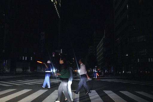 (AP Photo/Eugene Hoshiko). Police officers guide traffic as pedestrian walk in the blackout on the center of Sapporo city, Hokkaido, northern Japan, Thursday, Sept. 6, 2018. A powerful earthquake jolted Japan's northernmost main island of Hokkaido, buc...