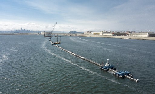 (The Ocean Cleanup via AP). In this Monday, Aug. 27, 2018 photo provided by The Ocean Cleanup, a long floating boom that will be used to corral plastic litter in the Pacific Ocean is assembled in Alameda, Calif. Engineers will deploy a trash collection...