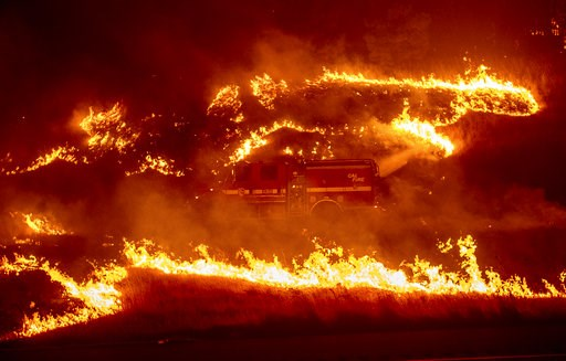 (AP Photo/Noah Berger). Flames from a backfire burn around a fire truck battling the Delta Fire in the Shasta-Trinity National Forest, Calif., on Thursday, Sept. 6, 2018.