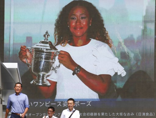 (AP Photo/Koji Sasahara). People walk by a huge screen showing US Open women's singles champion Naomi Osaka with her trophy, in Tokyo, Monday, Sept. 10, 2018.