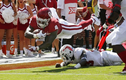 (AP Photo/Sue Ogrocki). Oklahoma running back Trey Sermon (4) dives over Florida Atlantic safety James Pierre (23) for a touchdown in the first half of an NCAA college football game in Norman, Okla., Saturday, Sept. 1, 2018.