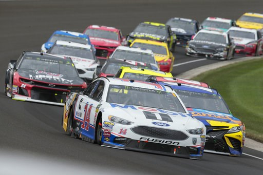 (AP Photo/AJ Mast). NASCAR Cup Series driver Clint Bowyer (14) leads a pack of cars through the first turn during the NASCAR Brickyard 400 auto race at Indianapolis Motor Speedway, in Indianapolis Monday, Sept. 10, 2018.