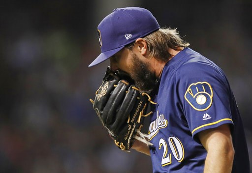 (AP Photo/Jim Young). Milwaukee Brewers' Wade Miley yells into his glove as he walks off the field at the end of the first inning of a baseball game Monday, Sept. 10, 2018, in Chicago.