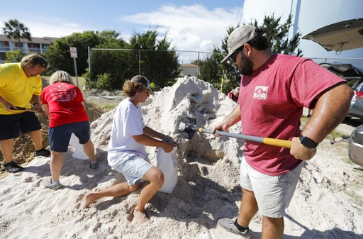 (AP Photo/Mic Smith). Walker Townsend, at right, from the Isle of Palms, S.C., fills a sand bag while Dalton Trout, in center, holds the bag at the Isle of Palms municipal lot where the city was giving away free sand in preparation for Hurricane Floren...