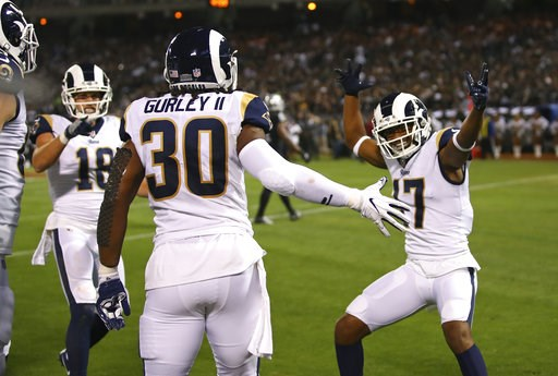 (AP Photo/Ben Margot). Los Angeles Rams running back Todd Gurley is greeted by teammates Cooper Kupp (18) and Robert Woods (17) after scoring a touchdown during the first half of an NFL football game against the Oakland Raiders in Oakland, Calif., Mond...