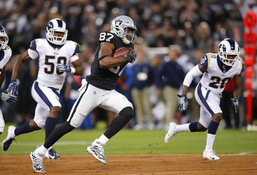 (AP Photo/John Hefti). Oakland Raiders tight end Jared Cook runs with the ball past Los Angeles Rams linebacker Samson Ebukam, left, and defensive back Lamarcus Joyner (20) during the first half of an NFL football game in Oakland, Calif., Monday, Sept....