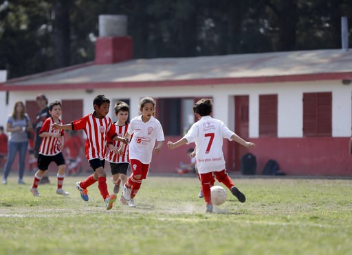 (AP Photo/Natacha Pisarenko). In this Sept. 8, 2018 photo Candelaria Cabrera, center, plays with her soccer teammates against the Alumni Club, in Chabaz, Argentina. While she's officially now banned from playing with Huracan because she is a girl, the ...