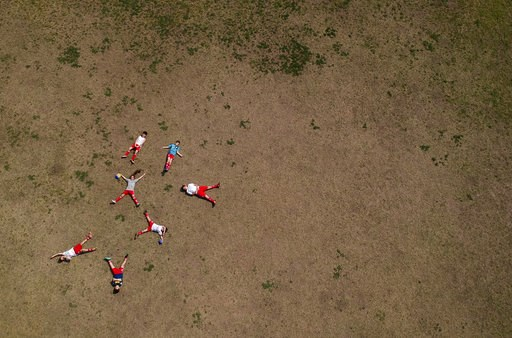 (AP Photo/Natacha Pisarenko). In this Sept. 8, 2018 photo, Candelaria Cabrera poses for a photo with her Huracan soccer club teammates in Chabaz, Argentina. Printed on the back of her jersey and on her red shorts is a number 4. But it's her long, coppe...