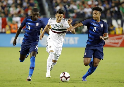 (AP Photo/Mark Humphrey). Mexico midfielder Roberto Alvarado (24) dribbles the ball past U.S. midfielders Tim Weah (11) and Weston McKennie (8) during an international friendly match, Tuesday, Sept. 11, 2018, in Nashville, Tenn.