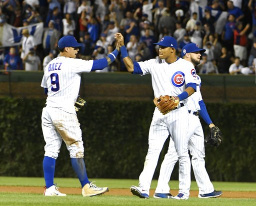 (AP Photo/David Banks). Chicago Cubs second baseman Javier Baez (9) and shortstop Addison Russell (27) celebrate their 3-0 win against the Milwaukee Brewers in a baseball game, Tuesday, Sept. 11, 2018, in Chicago.