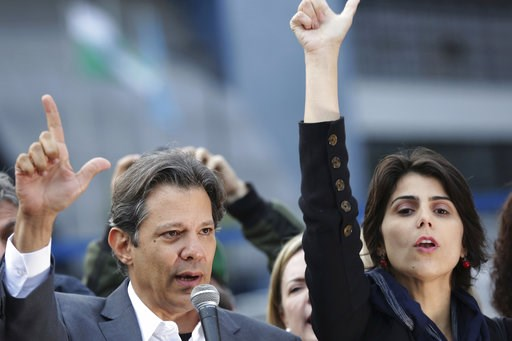 (AP Photo/Eraldo Peres). Workers' Party presidential candidate Fernando Haddad, left, and his running-mate Manuela d'Avila hold a campaign rally outside federal police headquarters where former President Luiz inacio Lula da Silva is in jail for corrupt...