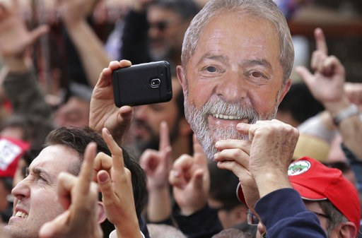 (AP Photo/Eraldo Peres). A supporter holds a mask in the likeness of the Brazil's jailed former President Luiz Inacio Lula da Silva, during a campaign rally outside federal police headquarters where da Silva is in prison for corruption, in Curitiba, Br...