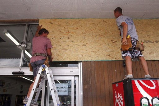 (Gray Whitley/Sun Journal via AP). Robert Patch and John Courtney, of Local Builder's Construction, install wood paneling over windows at the Armstrong Grocery , Tuesday, Sept. 11, 2018, in New Bern, N.C., as storeowners and residents prepare for Hurri...