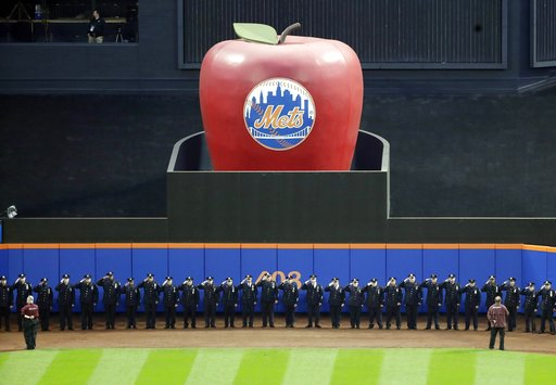 (AP Photo/Frank Franklin II). Members of the New York Police Department salute during the pregame ceremony of a baseball game between the New York Mets and the Miami Marlins, Tuesday, Sept. 11, 2018, in New York.