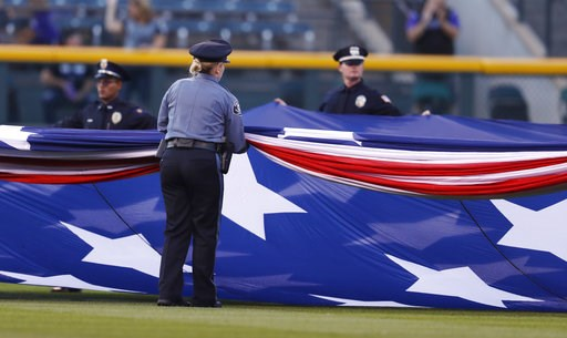 (AP Photo/David Zalubowski). Police officers unfurl an American flag to mark the anniversary of the 9/11 terrorist attacks during a ceremony before a baseball game against the Arizona Diamondbacks, Tuesday, Sept. 11, 2018, in Denver.
