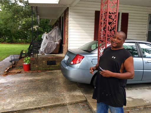 (AP Photo/Emery Dalesio). James Howell Jr. sizes up how to protect his home Tuesday, Sept. 11, 2018, in Princeville, N. C., from the approaching Hurricane Florence. The house was damaged by Hurricane Matthew in 2016. Howell said the furniture on his po...