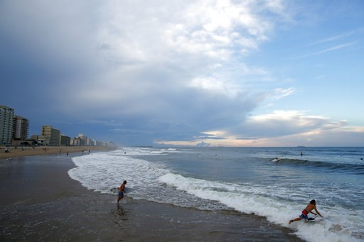 (AP Photo/Alex Brandon). Surfers head to the waves, Tuesday, Sept. 11, 2018, in Virginia Beach, Va., before the arrival of Hurricane Florence.