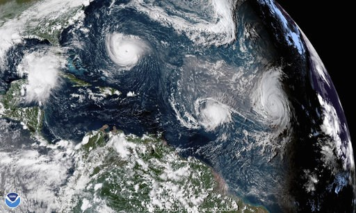 (NOAA via AP). CORRECTS DATE TO SEPT. 11, NOT 1 - This enhanced satellite image made available by NOAA shows Tropical Storm Florence, upper left, in the Atlantic Ocean on Tuesday, Sept. 11, 2018 at 3:30 p.m. EDT. At center is Tropical Storm Isaac and a...
